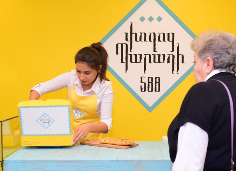 Frau in weißer Bluse und gelber Schürze vor einer gelben Wand verpackt etwas in einer gelben Schachtel. Eine ältere Dame im Bildvordergrund schaut ihr dabei zu.