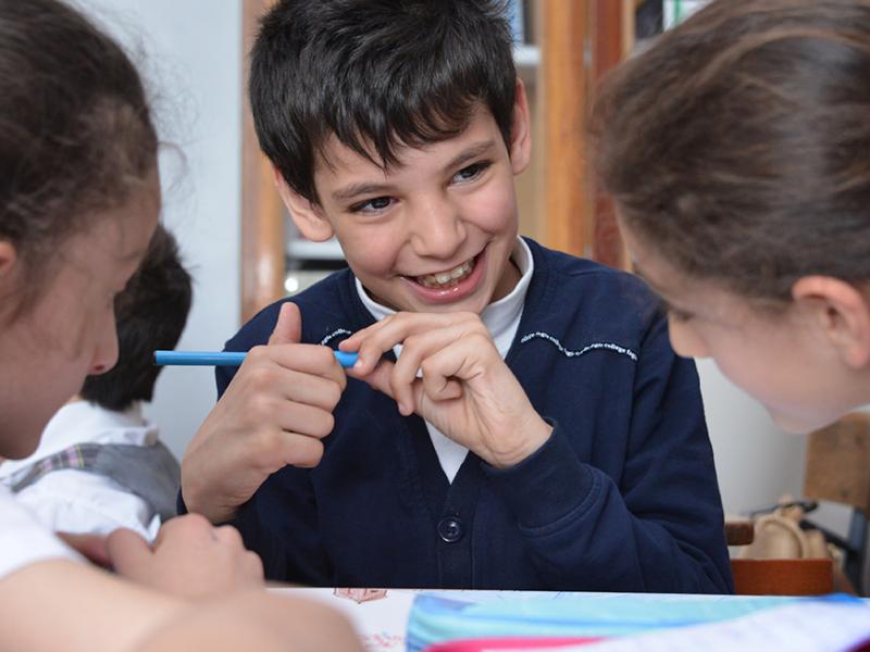 Drei Kinder. Ein Junge schaut lachend zu einem Mädchen im rechten Bildteil.