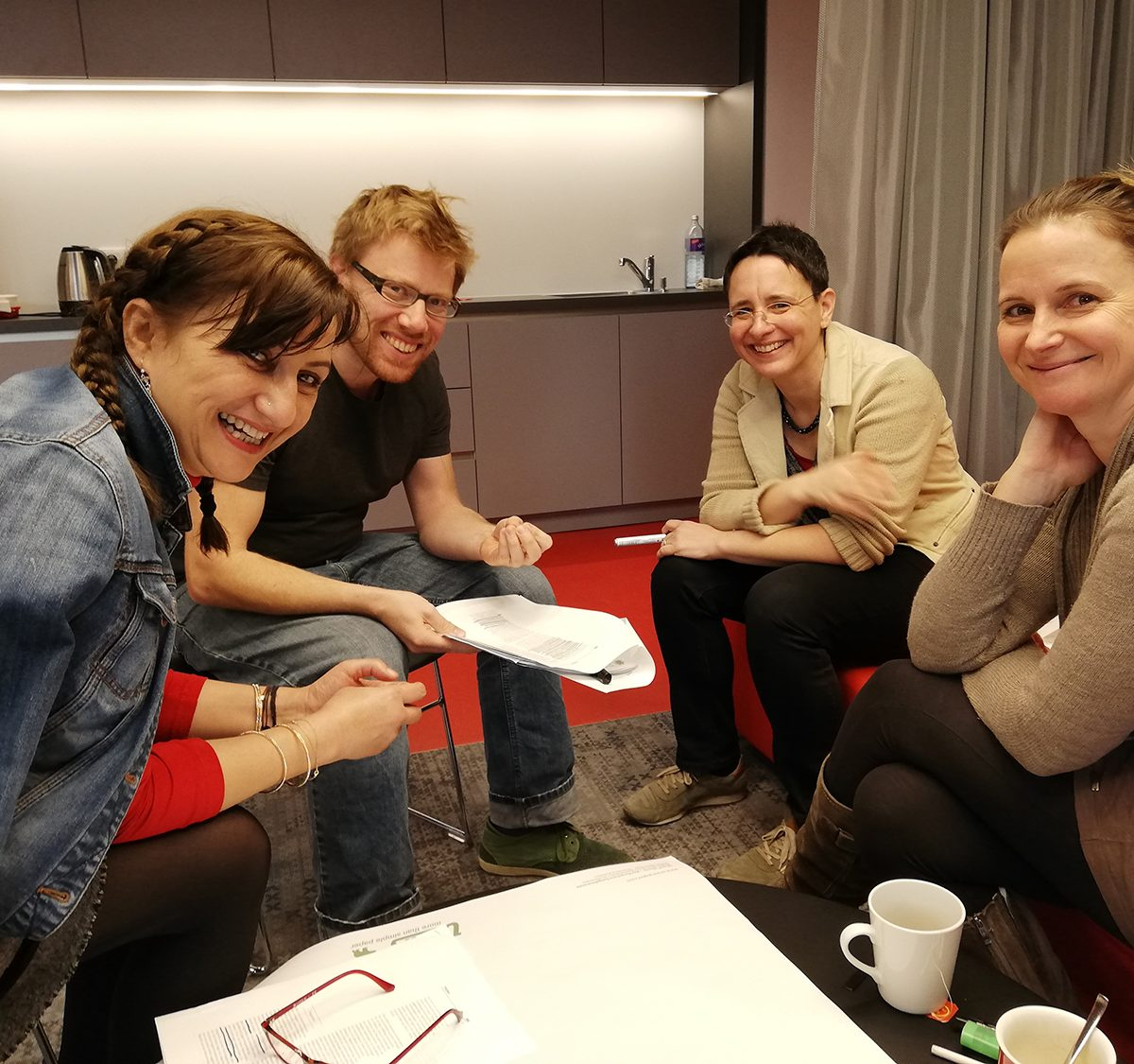 Vier Personen sitzen vor einer Küchenzeile im Halbkreis und lachen in die Kamera