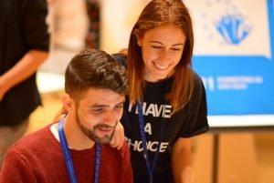 Junge Frau schaut jungem Mann über die Schulter, lächelnd