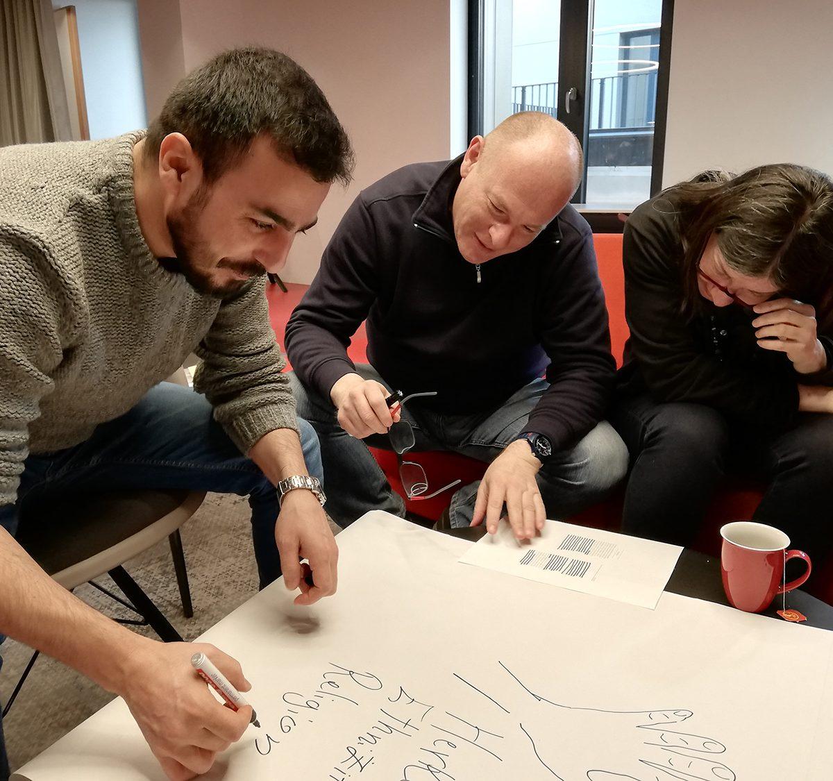 Drei Personen sitzen zusammen und schreiben Begriffe auf einen Flipchart