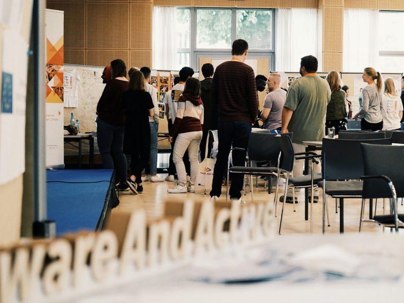 """Semminarraum mit Menschen im Hintergrund, die verschiedene Pinnwände anschauen und miteinander sprechen. Im Vordergrund ein Holzschnitt des """"Aware and Active"""" Logos"""
