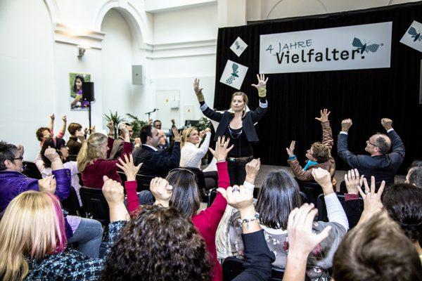 Publikum bei der vier Jahre Vielfalter-Feier streckt die Hände in die Luft