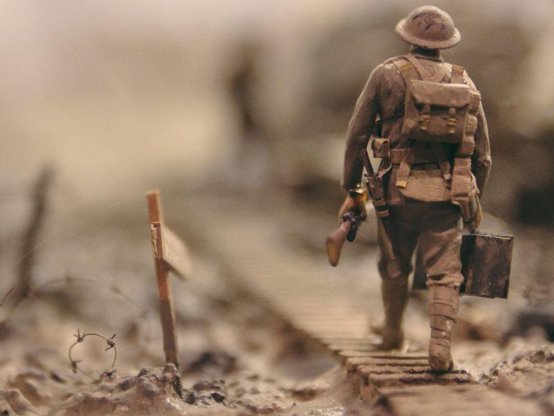 Modellfigur eines Soldaten aus dem Ersten Weltkrieg, über eine Brücke gehend. Daneben Stacheldraht und Erde.