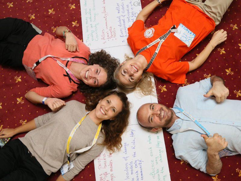 Vier Personen liegen sternförmig Kopf an Kopf auf dem Boden, auf dem auch ein beschriebener Flipchart liegt, lächelnd, aus Vogelperspektive