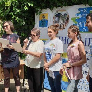Zwei ältere Frauen, zwei jugendliche Frauen und ein Mann stehen in einer Reihe, eine der älteren Frauen liest von einem Blatt und spricht in ein Mikrofon.