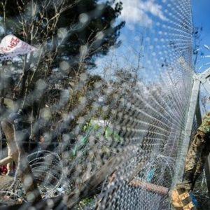 Ein Migrant demonstriert hinter einem Maschendrahtzaun, während ein Soldat Stacheldraht auf dem Zaun anbringt