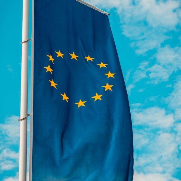 EU-Flagge auf Fahnenmast vor blauem Himmel mit wenigen Wolken aus Froschperspektive