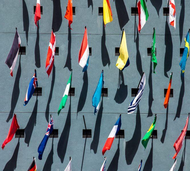 Europäische Fahnen auf horizontalen Fahnenstangen an einer grauen Wand, auf die sie ihre Schatten werfen