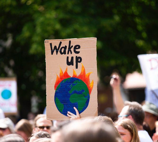 """Demonstration, bei der ein Pappschild mit einem brennenden Globus und der Überschrift """"Wake Up"""" hochgehalten wird"""