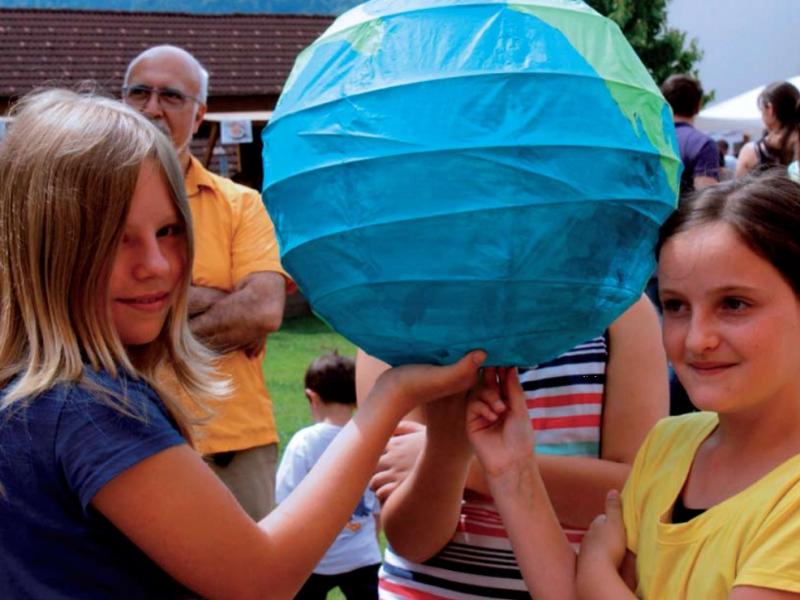 Kinder halten zu dritt einen Lampion, der wie ein Globus bemalt ist.