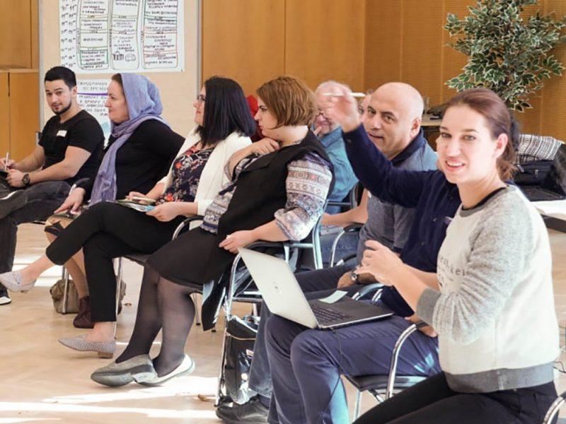 Personen in einem Sesselkreis in einem Veranstaltungssaal, im Hintergrund ein Roll-Up des IZ - Vielfalt, Dialog, Bildung