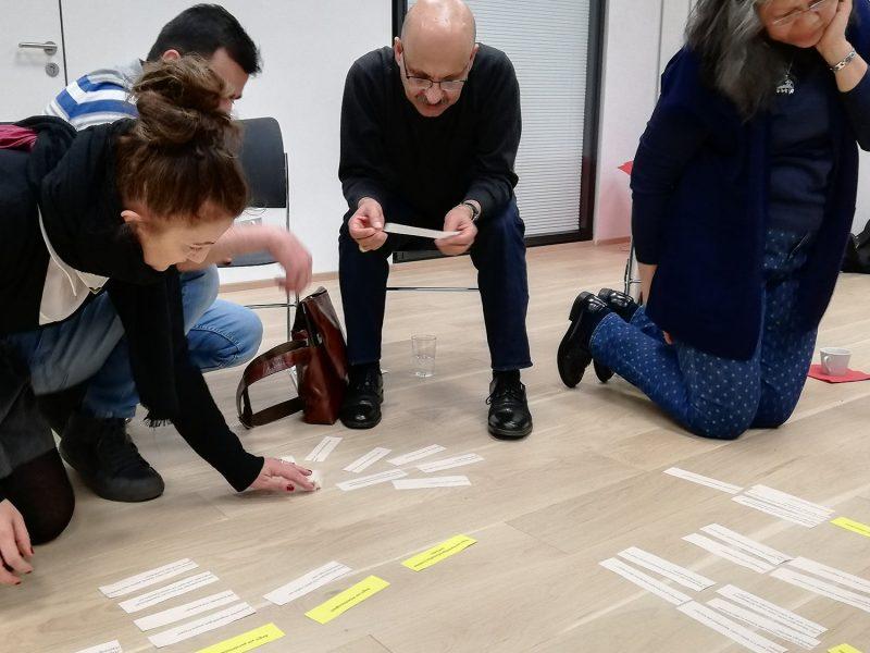 Vier Personen, auf Stühlen sitzend und am Boden knieend, arbeiten mit rechteckigen Papierstreifen unterschiedlicher Farbe.