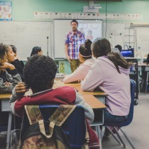 Klassenraum mit Kindern an Gruppentischen. Eine Lehrkraft im Bildhintergrund.