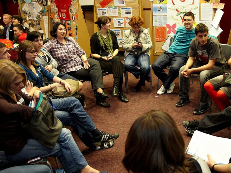 Personen im Sesselkreis sprechen miteinander, im Hintergrund befüllte Pinnwände