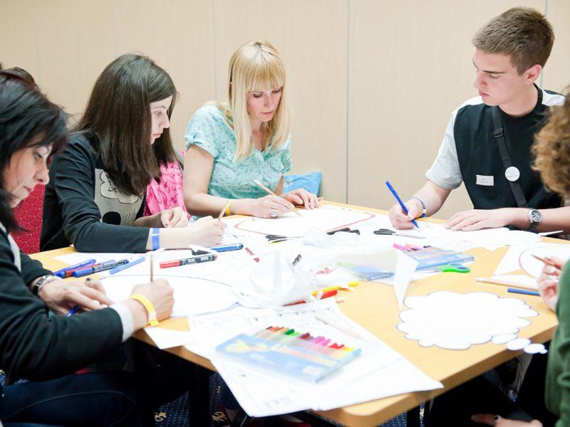 Lehrerinnen und Jugendliche schreiben mit Farbstiften auf Blätter, an einem Tisch sitzend