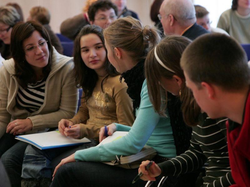 Lehrerin sitzt mit Schülerinnen in einer Reihe bei einer Veranstaltung, hört zu was eine der Schülerinnen zu ihr sagt