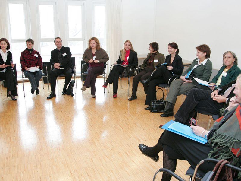 Lehrerinnen in einem hellen Seminarraum im Halbkreis sitzend