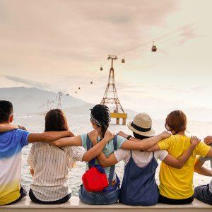 Projektfoto Erasmus+ Jugend in Aktion. Eine Gruppe Jugendlicher in einer Reihe auf einer Mauer sitzend halten sich gegenseitig an den Schultern. Sie blicken auf eine Meer-Enge zu einer Inselgruppe. Eine Seilbahn mit Gondeln verläuft in Richtung der Inselgruppe.
