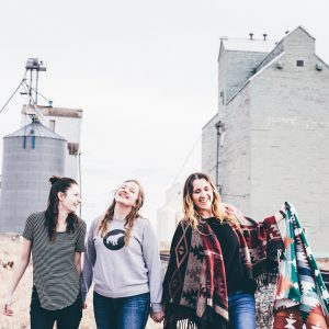 Projektfoto ESK. Drei junge Frauen gehen gelassen und lächelnd neben einem Bahngleis in einem Getreidefeld. Ein Getreidesilo und graue Gebäude im Hintergrund vor grauem Himmel.