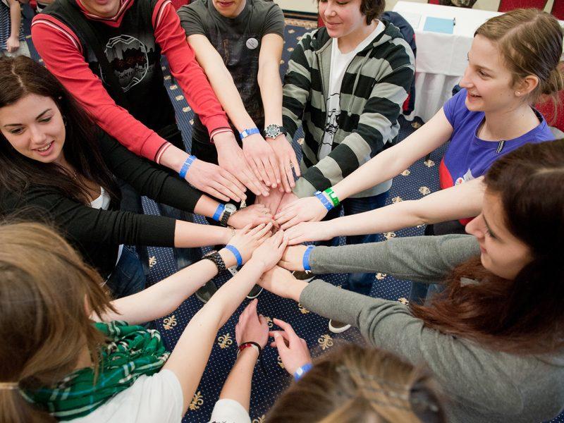 Acht junge Menschen im Kreis stehend, die Arme sternförmig zusammengestreckt
