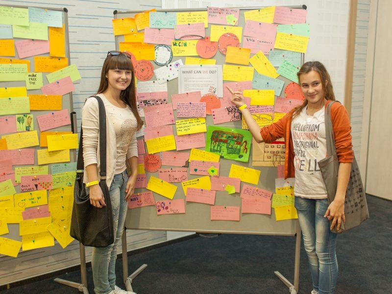 2 Schülerinnen vor einer mobilen Pinnwand mit aufgepinnten Notizkarten