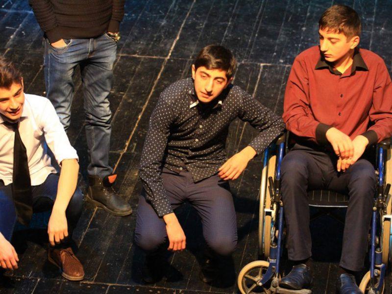 Vier junge Männer auf einer Bühne, einer steht, zwei hocken, einer sitzt im Rollstuhl.