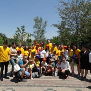 Gruppenfoto von rund 30 Jugendlichen, teilweise in gelben T-Shirts, im Halbkreis aufgestellt.