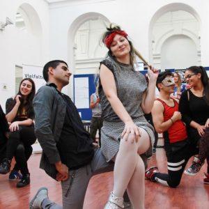 Tanzpaare in einer Halle mit Vielfalter-Roll-Ups im Hintergrund. Die Tanzpartnerinnen sitzen auf den ausgestreckten Knien der halbknieenden Männer.