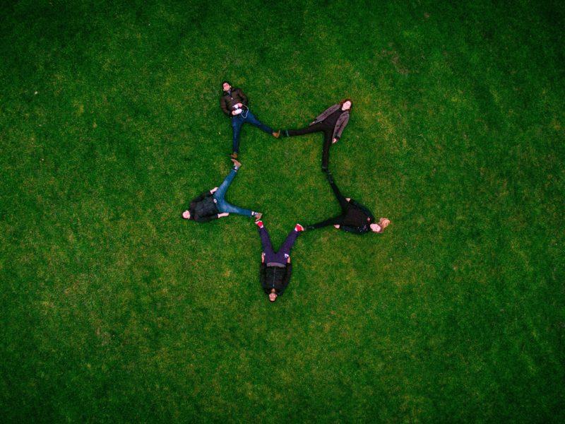 YouthNET CIS - Projektbild. 5 Personen auf der Wiese liegend, Vogelperspektive. Die Beine Formen gemeinsam einen Stern.